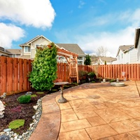 Fenced backyard with concrete tile floor deck and decorated flower bed